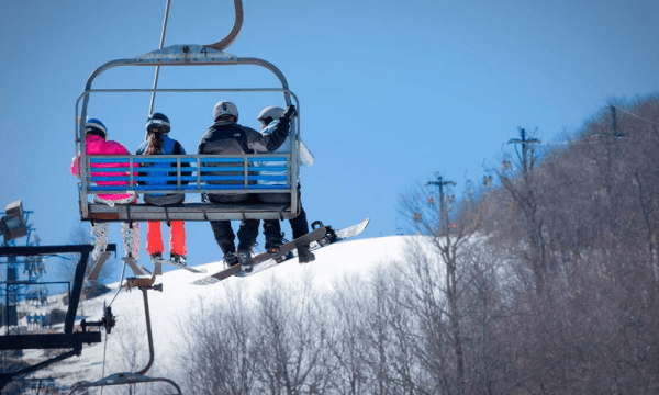 A family sits on a chairlift to take them to the top of the mountain for skiing