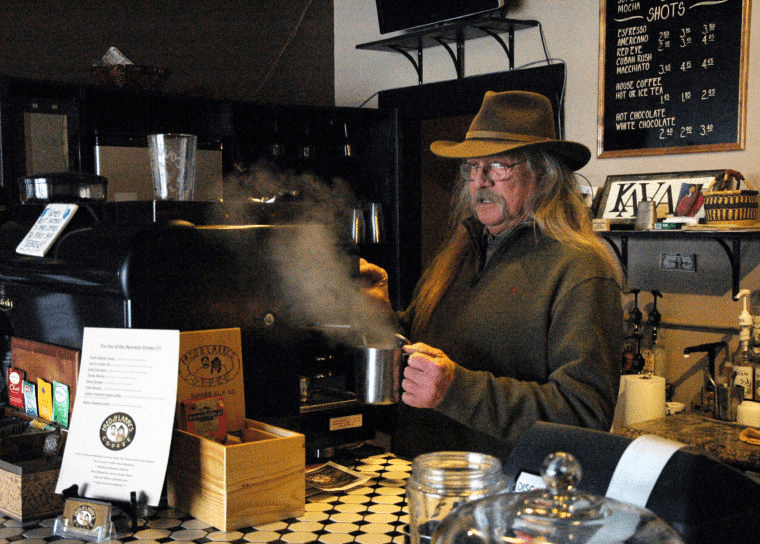 A barista with a cup of coffee at Fred & Larry's in Banner Elk